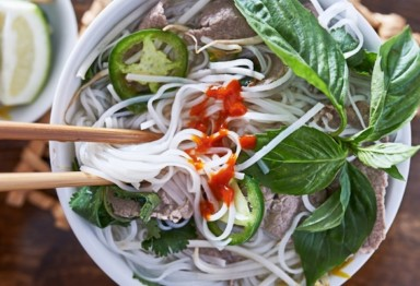 Eating bowl of pho with chopsticks
