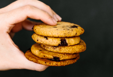 A hand holding a stack of cookies