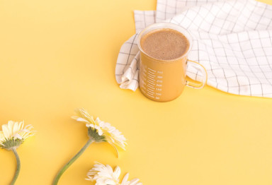 Cup of Bulletproof Coffee on yellow background