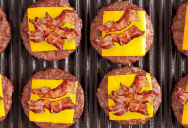 Burgers with cheese and bacon on grill