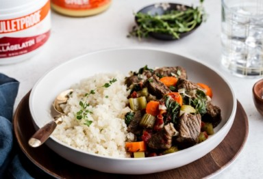 A plate of slow-cooked beef stew with cauliflower rice