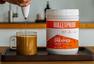 A milk frother mixing Bulletproof Original Creamer into a coffee mug