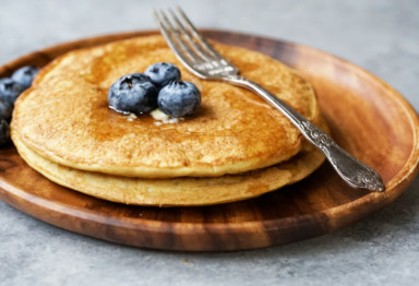 A short stack of blueberry pancakes with a fork