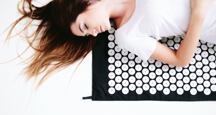 Woman laying on acupressure mat