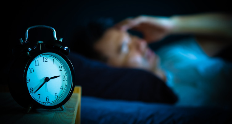 man in bed unable to sleep