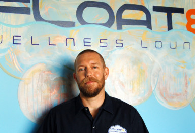 Matt Beck, owner of Float8 Wellness Lounge, standing in front of a branded mural
