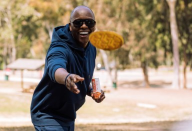 A black man throwing a frisbee outside with a can of Bulletproof Original Cold Brew Latte in his hand
