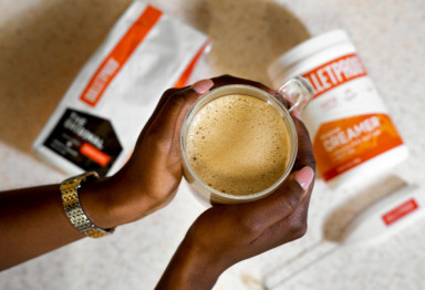 An overhead shot of hands holding a coffee cup and Bulletproof Coffee ingredients
