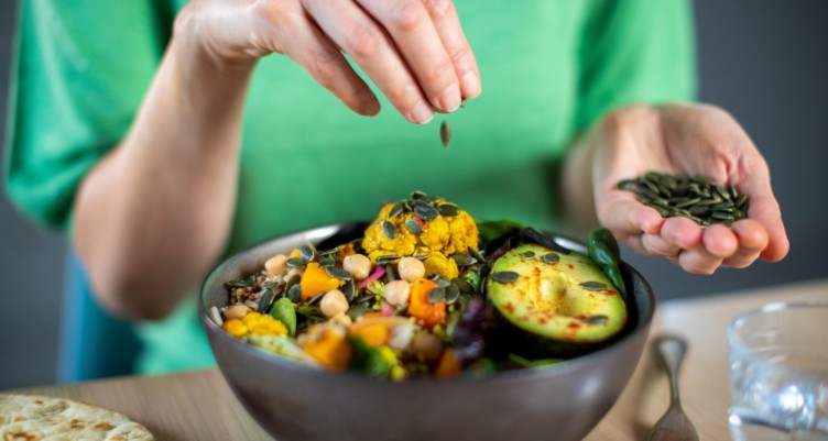 Woman adding pumpkin seeds to vegan meal in a bowl.