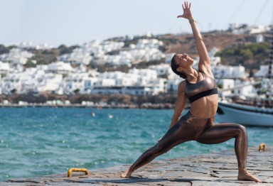 A girl stretching to the sky in a yoga pose on the water