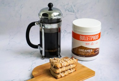 A French press, a stack of scones and a tub of Bulletproof Hazelnut Creamer